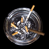 Ashtray with cigarettes and tobacco. Over black background royalty free stock image