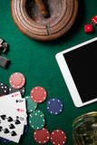 Ashtray, digital tablet, dice, casino chips and playing cards on poker table. In casino Stock Images