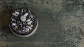 Ashtray. Filled up with stubs, placed on wooden background Stock Photos