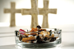 Ashtray full of burnt cigarettes, three crosses in background Stock Photos