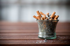 Ashtray full with butts. On dirty table Royalty Free Stock Images
