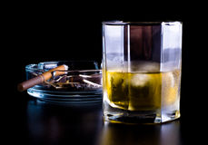 Ashtray full of butts and glass of whiskey Stock Images