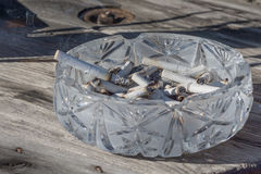 Ashtray full of cigarette butts. Ashtray with smoking cigarette, butts and ashes Royalty Free Stock Photography
