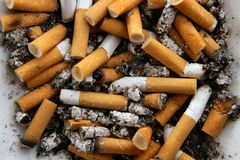 Ashtray full of cigarettes. Dirty tobacco texture Stock Photo