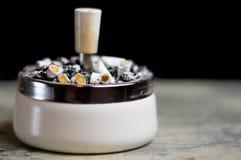 Ashtray full of cigarettes. Ashtray with loads of cigarettes in it, addictive drugs Stock Image