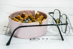 Ashtray and glasses on white blueprint background Royalty Free Stock Image