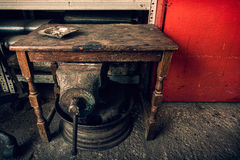 Ashtray on a  grunge wooden table in a junkyard with old mechani. Cal tools Royalty Free Stock Photos