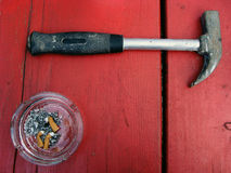 Ashtray and hammer. On red background Stock Photos