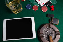 Ashtray, lighter, digital tablet, dice, casino chips and playing cards on poker table. In casino Stock Photos
