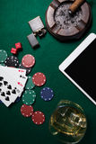 Ashtray, lighter, digital tablet, dice, casino chips and playing cards on poker table. In casino Stock Image