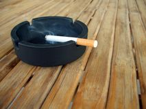 Ashtray with lit cigarette. On a wooden table Royalty Free Stock Images