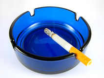 Ashtray with lit cigarette. Isolated on white Royalty Free Stock Photography