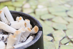 Ashtray with a lot of cigarettes on the floor Royalty Free Stock Photography