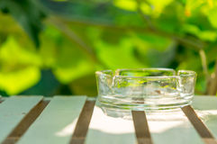 Ashtray made of glass on table.  Royalty Free Stock Photography