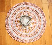 Ashtray made out of big seashell lying on home-made crocheted tablecloth. Vintage royalty free stock photography
