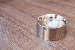 Ashtray. Metal ashtray on brown wooden table Stock Image