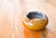 Ashtray on the table. An ashtray filled with smoked cigarettes on a wooden table Stock Image