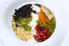 Ashura Pudding. Wheat dessert with dried nuts and fruits. Turkish sweet Ashura Noah`s pudding in a bowl with pomegranate seeds stock photo