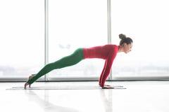 Ashva Sanchalasana Den härliga plankan för yogakvinnaövning poserar i ett stort fönster Royaltyfria Bilder