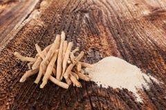 Ashwagandha roots and powder. Ashwagandha roots and powder on wooden table. Superfood concept Royalty Free Stock Photography