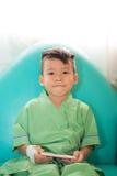 Asiático 3 años de sonrisa del niño y teléfono móvil del juego después de la recuperación Imágenes de archivo libres de regalías