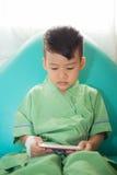 Asiático 3 años de sonrisa del niño y teléfono móvil del juego después de la recuperación franco Imagen de archivo libre de regalías