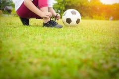 Asiático da criança que amarra sapatas com a bola na grama verde Fotografia de Stock Royalty Free