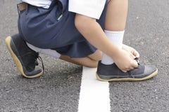 Asiático da criança que amarra sapatas na borda da estrada Imagem de Stock Royalty Free