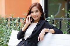 Asiático de la empresaria que usa el teléfono para el celling y mandando un SMS en su teléfono móvil fotografía de archivo libre de regalías