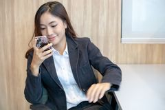 Asiático de la empresaria que usa el teléfono para el celling y mandando un SMS en su m imágenes de archivo libres de regalías
