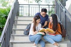 Asiático de la universidad de los estudiantes junto que lee estudio del libro fotos de archivo