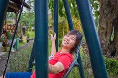 Asiático embarazada hermoso - mujer china que sonríe jugando el oscilación o Imágenes de archivo libres de regalías