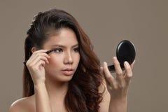 Asiático femenino que aplica el trazador de líneas del ojo Imagen de archivo libre de regalías