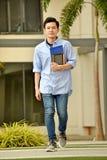 Asiático inteligente Person Walking On Campus de la universidad fotos de archivo libres de regalías