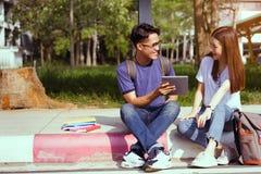 Asiático joven de los estudiantes junto usando el ordenador portátil imagen de archivo libre de regalías