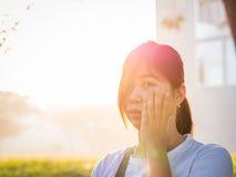Asiático joven hermoso - la mujer china que sostiene la mejilla, tiene un toque de bocina Imagen de archivo