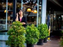 Asiático joven hermoso - mujer china que piensa en terraza Fotografía de archivo
