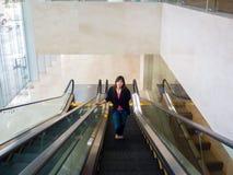 Asiático joven hermoso - mujer china que sonríe en la escalera móvil Foto de archivo