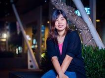Asiático joven hermoso - mujer china que sonríe en parque en la noche Fotografía de archivo