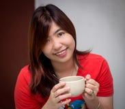 Asiático joven hermoso - mujer china que sostiene la taza Fotos de archivo libres de regalías