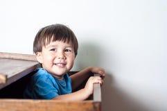 Asiático, menino da criança da raça misturada que espreitam para fora ou uma caixa de brinquedos de madeira Imagens de Stock Royalty Free
