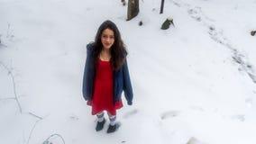 Asiático novo adolescente no vestido vermelho cercado pela neve foto de stock