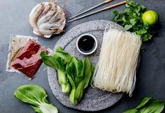 Asiático que cocina los ingredientes: tallarines de arroz, pok choy, salsas, camarones crudos Cocina china o tailandesa del conce imagen de archivo libre de regalías