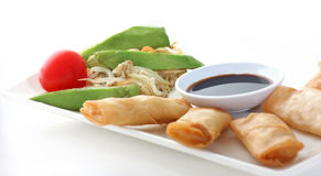 Asia. Spring rolls with soy sauce and a salad Stock Photos