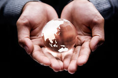 Asia and Australia continent. Hands holding a glass globe showing Asia and Australia continent Stock Photo