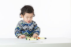 Asia baby boy concentrate on drawing. Isolated on white Royalty Free Stock Photos