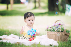 Asia Baby boy sitting on green grass with soap bubbles Stock Photos