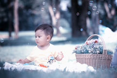 Asia Baby boy sitting on green grass with soap bubbles Royalty Free Stock Images