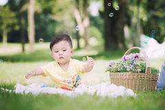 Asia Baby boy sitting on green grass with soap bubbles Royalty Free Stock Photography