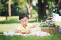 Asia Baby boy sitting on green grass with soap bubbles Stock Images